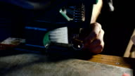 Sewing process of the leather belt. Man's hands behind sewing video