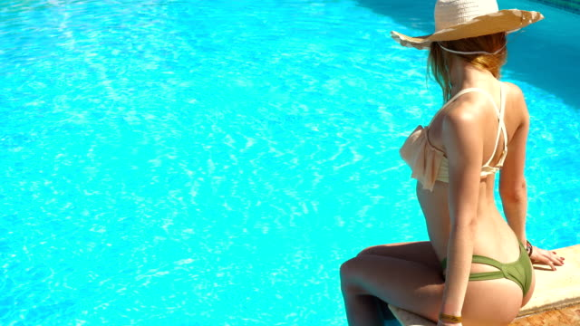 sexual young lady in straw hat and seductive swimsuit sits by the blue pool video
