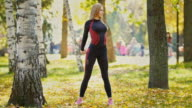 Sexy Attractive female blonde bikini-fitness model stretching in the autumn park on ground covered yellow leaves - stretching arms video