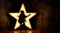 sexy blonde girl with electric guitar in leather, shining star in the background, slow motion, silhouette video