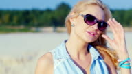 Sexy blonde woman in sunglasses, posing for the camera at the beach video