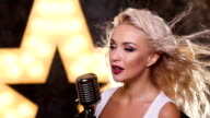 sexy blonde woman Singing with Retro Microphone, shining star in the background, slow motion, close up video