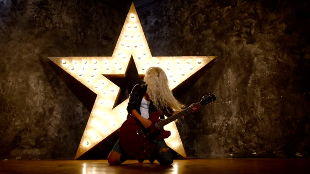 sexy blonde woman wearing leather jacket and playing a guitar, slow motion, silhouette video