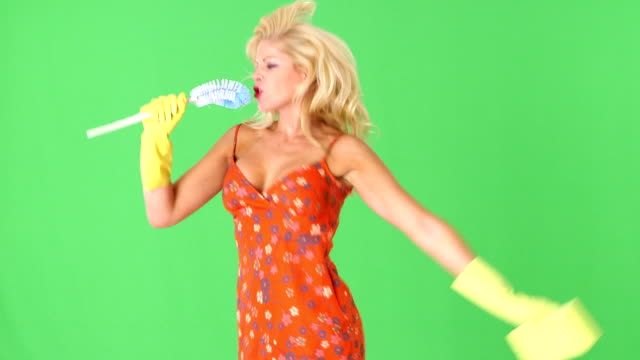 Sexy blonde woman with toilet bowl brush and sponge, singing video