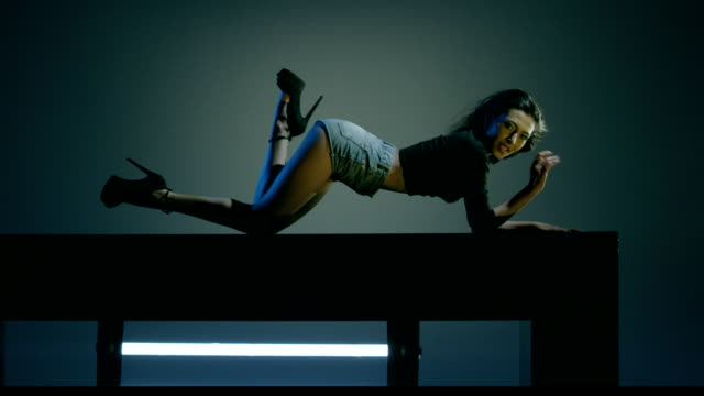 Sexy brunette dances on blue dark background. Beautiful girl dancing, laying on cube. Shot on RED EPIC DRAGON Cinema Camera in slow motion. video