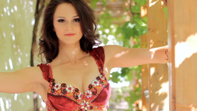 Sexy brunette with tattoos dancing belly dance in gazebo, slow motion video