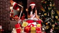 sexy girl and a lot of Christmas gifts, cute Santa Claus girl, chooses a gift for you, gift presentation, packed festive boxes, background video
