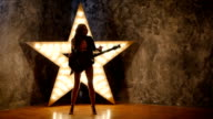 sexy girl dancing and posing with electric guitar, shining star in the background. slow motion, silhouette video