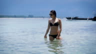 Sexy girl in black bikini and sunglasses standing in blue sea, thoughtfully passing her hand over the water and bathing in the sun of Bali. Brunette in black swimsuit enjoying her jorney in Indonesia video