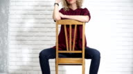 Sexy girl is sitting on a chair adjusting his glasses video