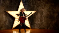 sexy girl with electric guitar in leather, shining star in the background, slow motion video