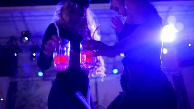 sexy girls holding glasses with cocktails and dance at night club, beautiful women with beverage on party in disco lights video