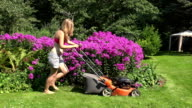 Sexy woman cuts the grass with petrol lawn mower around red flower bed. FullHD video