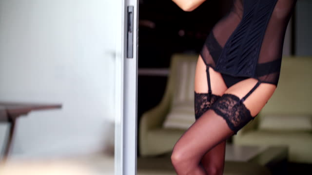 Sexy woman in lingerie and tights is standing in door video