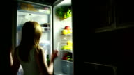 sexy Woman opens the refrigerator at night. selects a cucumber video