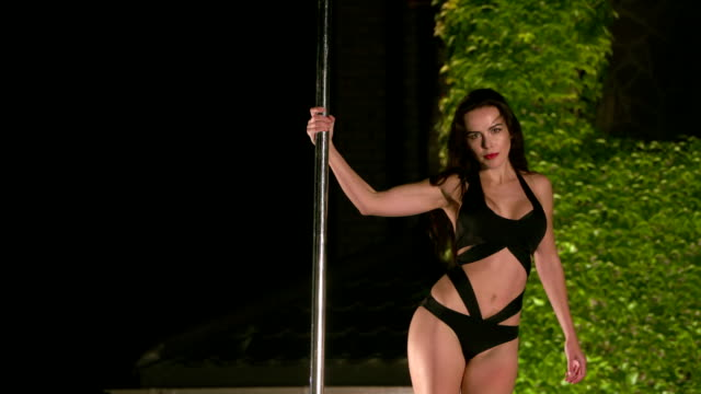 Sexy woman pole dancer in monokini performs pole dance poses video