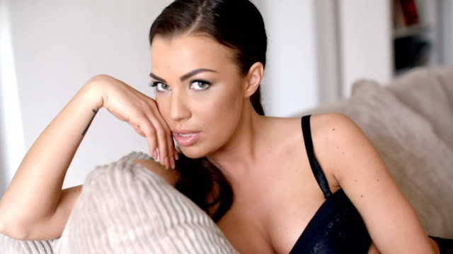 Sexy Woman Sitting on Sofa Leaning on her Hand video