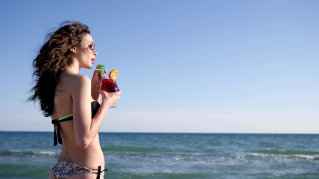 sexy woman with curly hair drinks colorful cocktail, Portrait of smiling girl on beach, shiny sea background video