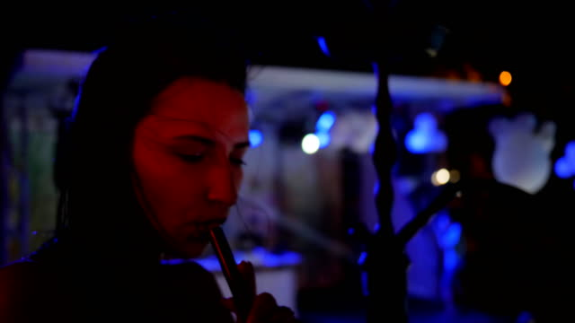 sexy young woman smoke a hookah on party in blue lights, beautiful female inhales taste of tobacco at night party video