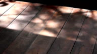 Shadow leaves on a wooden board. video