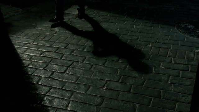 Shadow of a man walking on cobblestone way video
