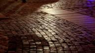 Shadows of people walking in a cobblestone street video