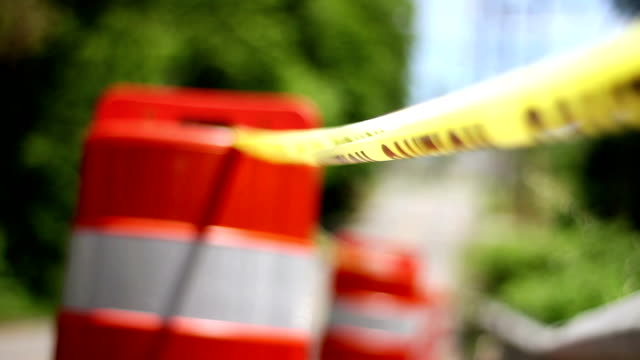 Shallow depth of field on construction barrel cones and caution tape on road video
