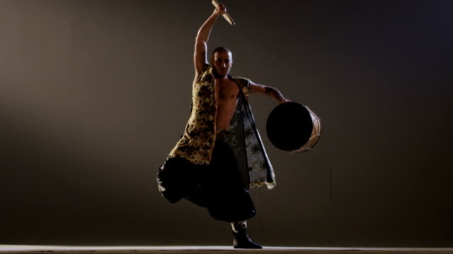 Shaman dancing with a drum on grey background. Ethnic Asian Dance. Shot on RED EPIC DRAGON Cinema Camera in slow motion. video