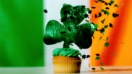 Shamrock confetti falling on st patricks day cupcake close up video