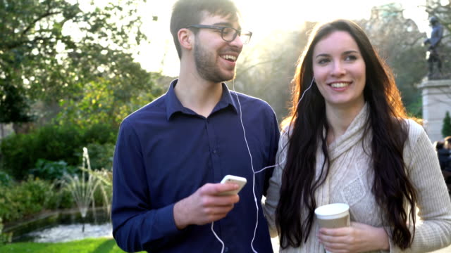 Sharing music, couple in the park. video