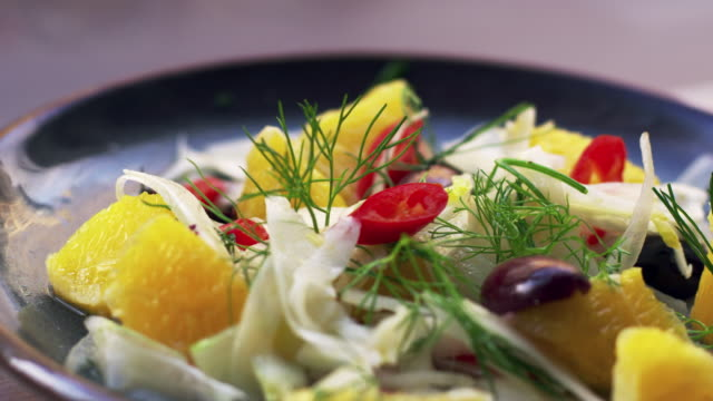 Shaved fennel and orange salad on plate, close up pan video