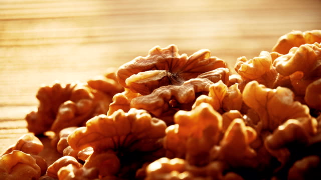 Shelled walnuts on a wooden table on a sunny day. FullHD macro shot video