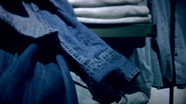 Shelves with denim clothes in the store video