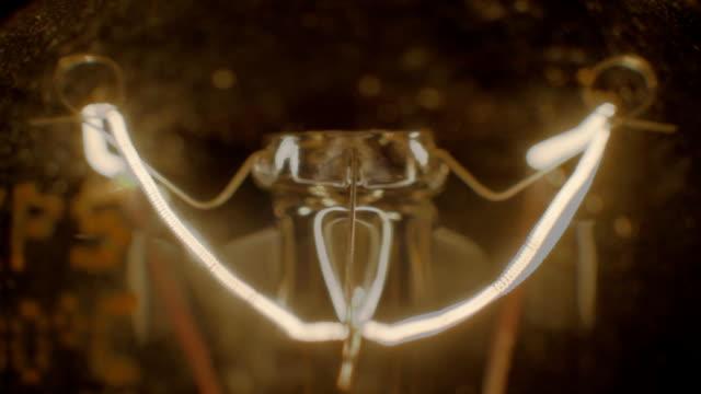 Shimmering light bulb extreme close up, spiral vibrating inside video