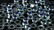 Shiny nuts and washers rotating on a black background. Seamless loop. Prores 4K video