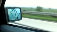 Shipping transportation trucking vehicles traveling on the highway, view in car rear-view mirror video
