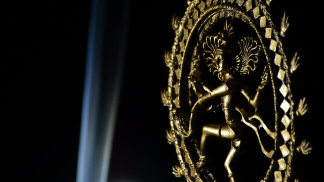 Shiva deity buddhist in rotation over black background with a smoke column video