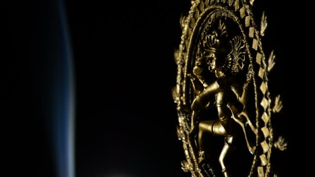 Shiva, deity of buddhism religion, rotating with smoke on black background video
