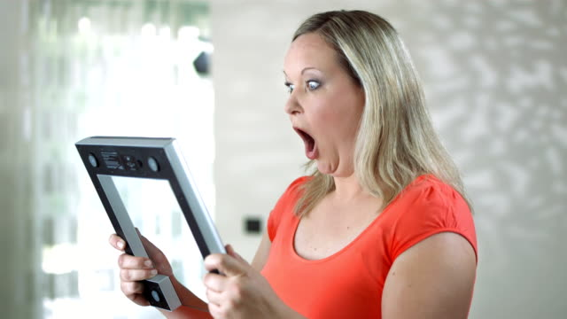HD DOLLY: Shocked Woman Looking At Bathroom Scale video