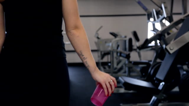 Shooting from back woman walking drinking water in gym video