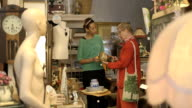 Shop assistant helps senior woman in antiques store video