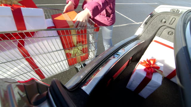 Shopper girl with shopping cart full of gift boxes loads car trunk video