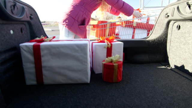 Shopper with shopping cart full of gift boxes loads car trunk video