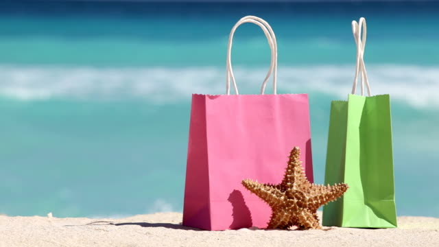 Shopping bags and starfish on sand against turquoise caribbean sea water video