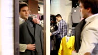 Shopping man in front of a mirror holding suit video