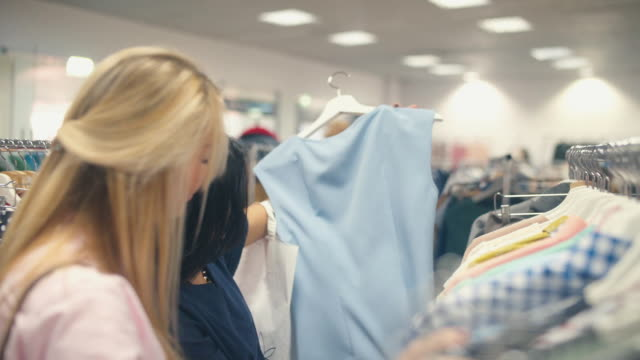 Shopping. Rail with clothes. Woman spending time in the shop video
