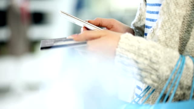 Shopping woman holding a Smartphone and Credit card video