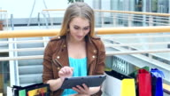 Shopping Woman holding Digital Tablet on bench the trading floor. Slow motion video