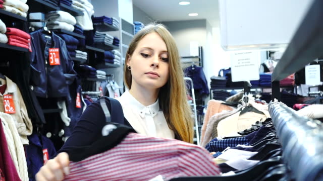 Shopping woman. Shopper looking at clothes in clothes store. Medium shot, handheld, slow motion 60fps. video