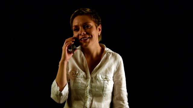 Short hair girl talking by mobile phone over black video